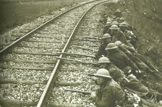 British troops take up position behind a railroad embankment