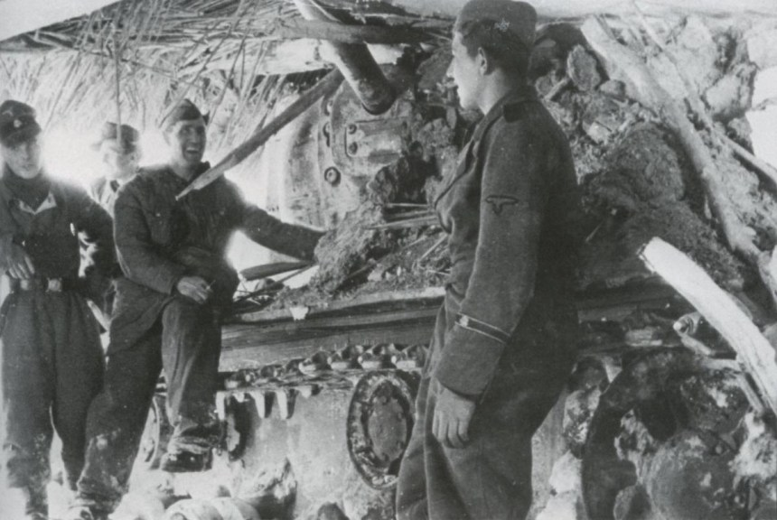 Death head's soldiers inspect a KV tank that they knocked-out