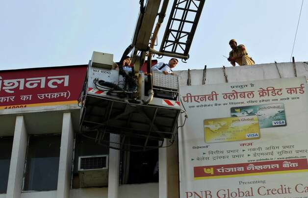 People are evacuated in a hydraulic ladder after a fire broke out in a multi-storey building housing the Punjab National Bank at Parliament Street in New Delhi, India, Wednesday. No deaths were reported but some of the injured, who had trouble in breathing, have been taken to hospitals according to local news reports. (AP Photo/Saurabh Das) Photo: Associated Press / SL