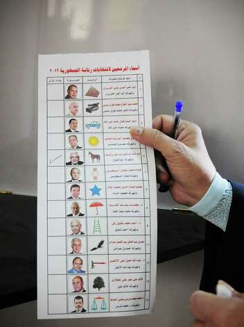An Egyptian woman holds a ballot paper with names of the 13 presidential candidates inside a polling station, in Giza, Egypt, Wednesday. More than 15 months after autocratic leader Hosni Mubarak's ouster, Egyptians streamed to polling stations Wednesday to freely choose a president for the first time in generations. (AP Photo/Mohammed Asad) Photo: Mohammed Asad, Associated Press / AP2012
