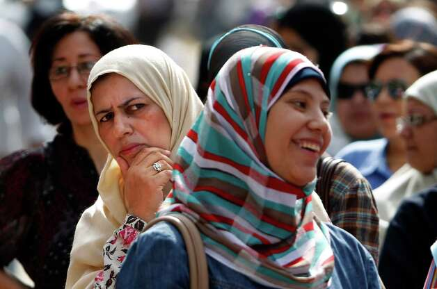Egyptian women wait to vote at Ibn Nafis Language School polling station in Nasr City, Cairo, Egypt, Wednesday. More than 15 months after autocratic leader Hosni Mubarak's ouster, Egyptians streamed to polling stations Wednesday to freely choose a president for the first time in generations. Waiting hours in line, some debated to the last minute over their vote in a historic election pitting old regime figures against ascending Islamists.(AP Photo/Fredrik Persson) Photo: Fredrik Persson, Associated Press / AP