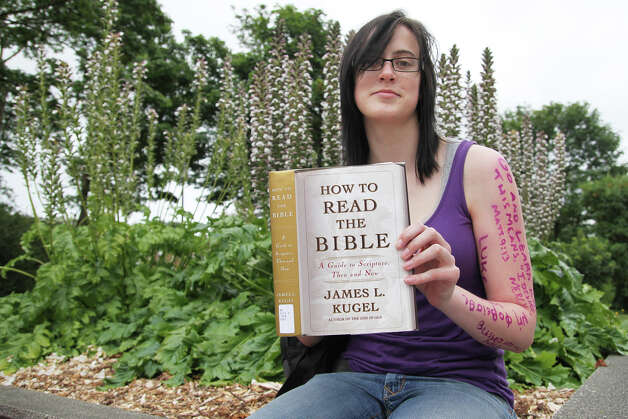 """In silent protest, Fred Demien holds up """"How To Read The Bible"""" by James L. Kugel. As a youth director of a Portland church, Demien believes that Westboro sends the wrong message about God and religion"""