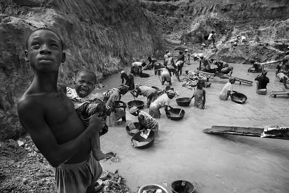 Families carry their children while they toil for free in mercury-poisoned pits to pan gold in Ghana. Photo: Lisa Kristine, Lisa Kristine ©