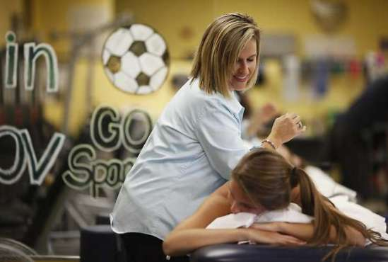 Senior physical therapist Robin Bousquet helps Kelly Furay with her back. Furay, a former volleyball player, quit the sport last year due to injury. Photo: James Tensuan, SFC