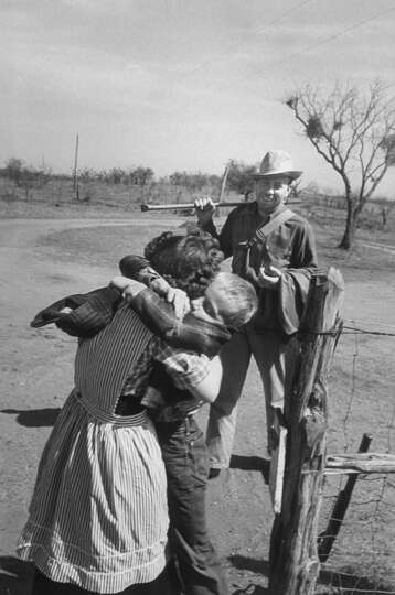 Author Fred Gipson with his son Mike who is hugging his mother after coming home from coon hunt, 194