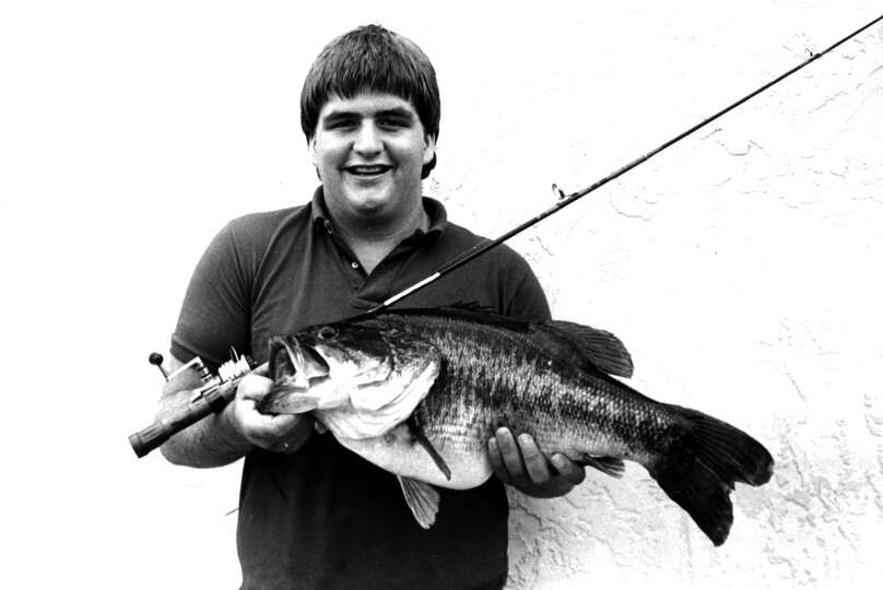 A boy stands holding a fishing rod and a 12 pound 6 ounce largemouth bass he caught on August 19, 19