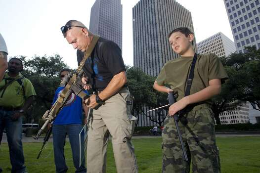 Ed Aldredge of Sugar Land, Texas, checks to make sure he doesn't have a round in the chamber of his AR-15 rifle, next to his son, Austin, 11, who was holding his .22 caliber rifle as they join a group of about 25 people with the gun rights organization Come and Take it Houston for a rally at City Hall in Houston Thursday, July 4, 2013(AP Photo/Houston Chronicle, Johnny Hanson) Photo: Associated Press
