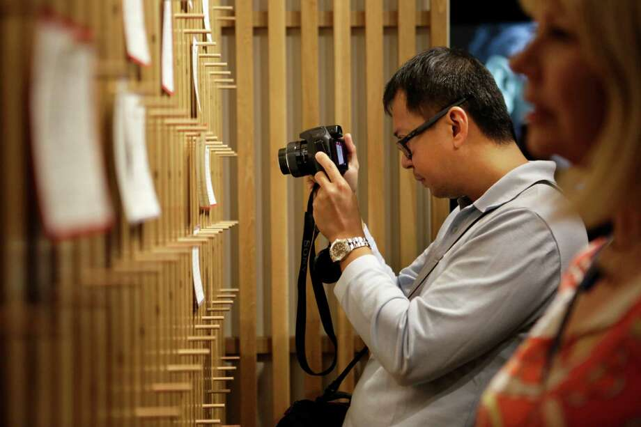A man takes a photo at the opening of an exhibition on Operation Babylift at the Presidio Officers Club in San Francisco. Photo: Terray Sylvester / The Chronicle / ONLINE_YES