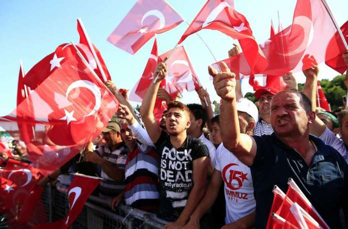 "Men chant slogans and wave flags as they take part in the ""National Unity March"" the one year anniversary of the July 15, 2016 botched coup attempt, in Istanbul, Saturday, July 15, 2017. Turkey commemorates the first anniversary of the July 15 failed military attempt to overthrow Turkey's President Recep Tayyip Erdogan, with a series of events honoring some 250 people, who were killed across Turkey while trying to oppose coup-plotters. (AP Photo/Lefteris Pitarakis) Photo: Lefteris Pitarakis, Associated Press"