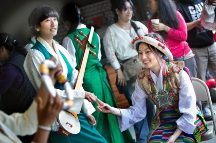 A performer holds the dramyin, a traditional Himalayan lute.