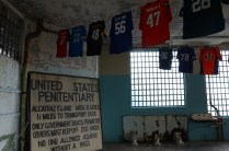 "NFL jerseys are suspended in the New Industries Building on Alcatraz Island on Tuesday, October 25, 2016. The peeling paint and toilet remains helped some guests fully appreciate the message of the abstract art installation ""Shortening: Making the Irrational Rational"" that the jerseys were a part of."