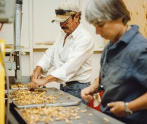Thoerner and farmworker Raymundo Montoya work together to sort shells from walnut pieces as they come through the cracking machine.