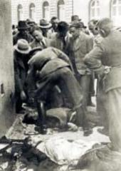 dead paratroopers were carried out in front of the crypt, Karl Hermann Frank is beding over one of the corpses