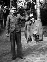 04-German-officer-holds-tattered-remains-of-uniform-worn-by-one-of-Hitlers-top-officers-after-failed-assassination-20.7.44-222x300
