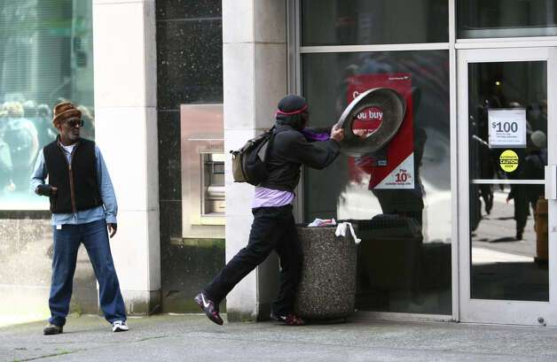 A black-clad protester attempt to break windows on a Bank of America during a May Day rally on Tuesday, May 1, 2012 in downtown Seattle. Photo: JOSHUA TRUJILLO / SEATTLEPI.COM