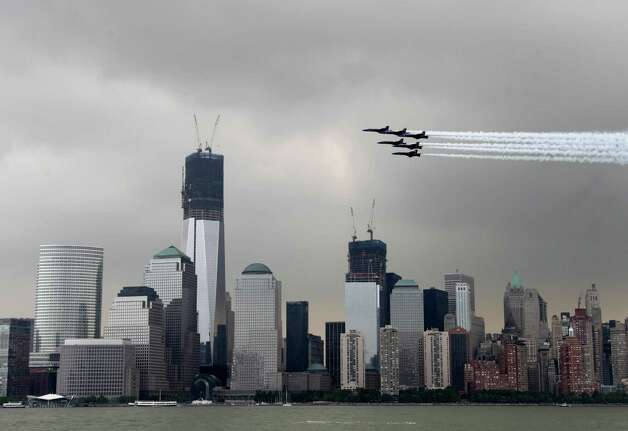 Military aircraft fly in formation in front of the lower Manhattan skyline and the World Trade Center site as seen from Jersey City, N.J., Wednesday. Naval vessels ranging from a U.S. amphibious assault ship to a Finnish minelayer are participating in New York City's Fleet Week. (AP Photo/Seth Wenig) Photo: Associated Press / SL