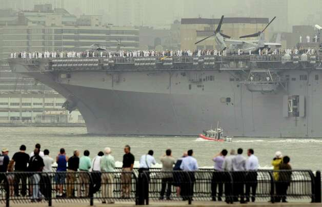 People watch the USS Wasp sail up the Hudson River from Jersey City, N.J., Wednesday. Naval vessels ranging from a U.S. amphibious assault ship to a Finnish minelayer are participating in New York City's Fleet Week. (AP Photo/Seth Wenig) Photo: Associated Press / SL