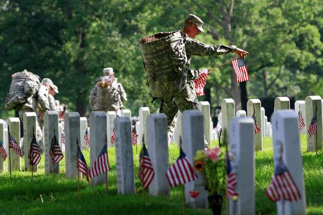 """Army Sgt. Brian Ellis, 22, of Canyon Lake, Texas, a soldier with the 3rd U.S. Infantry Regiment, or """"Old Guard,"""" places a flag before each grave in preparation for Memorial Day, during the annual """"Flags-In"""" at Arlington National Cemetery in Arlington, Va., on Thursday, May 24, 2012. Photo: Jacquelyn Martin, Associated Press / AP"""