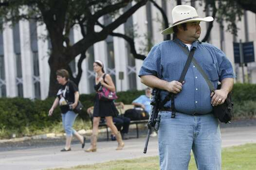 """Oscar Garza, 29, of Houston waits holding his AR-15  rifle as he joined a group of more than 20 people with the pro-gun organization, Come and Take it Houston, assembled at City Hall before walking through downtown carrying their guns as part of their rally Thursday, July 4, 2013, in Houston.<br /><br /><br /> """"The idea is to show people their rights and it's a way to educate them,"""" Garza said. """"The best gun safety is education.<br /><br /><br /> """"This is a Come and Take it Houston walk to help inform citizens about the gun laws here in Texas,"""" co-organizer Kenneth Lindbloom said. """"In Texas there are no restrictions on the open cary of long arms like rifles and shotguns. We want people to realize that in the hands of good people, guns are not dangerous and they don't kill people. When good people have guns it serves as a deterrent to stop crime.""""( Johnny Hanson / Houston Chronicle ) Photo: Houston Chronicle"""