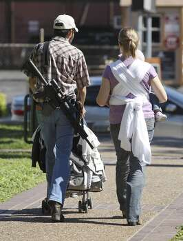 A gun owner and his wife leave a rally at Travis Park as part of the Come And Take It San Antonio pro-gun rally on Saturday, Oct. 19, 2013. Several hundred pro-gun owners displayed their rifles and long arms at a rally on the grounds of the Alamo. The group later marched to Travis Park where the event concluded. (Kin Man Hui/San Antonio Express-News) Photo: San Antonio Express-News