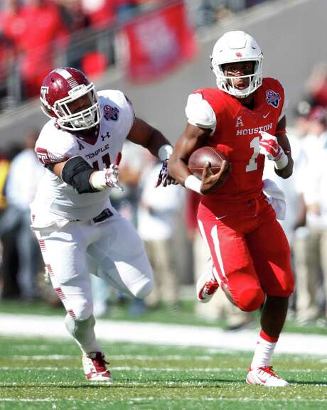Greg Ward Jr., right, was an elusive target for Temple defenders like linebacker Jarred Alwan. The UH quarterback rushed for 148 yards on 17 carries. Photo: Karen Warren, Staff / © 2015  Houston Chronicle