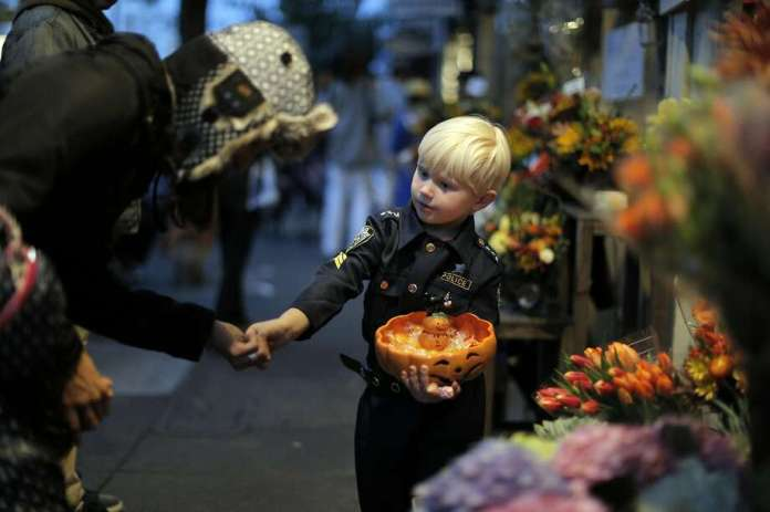 Vitaly Van De Sande, 4, hands out candy to passersby at his mom and grandmother's flower shop on 24th Street as the city celebrated Halloween in San Francisco, Calif., on Monday, October 31, 2016. Photo: Carlos Avila Gonzalez, The Chronicle