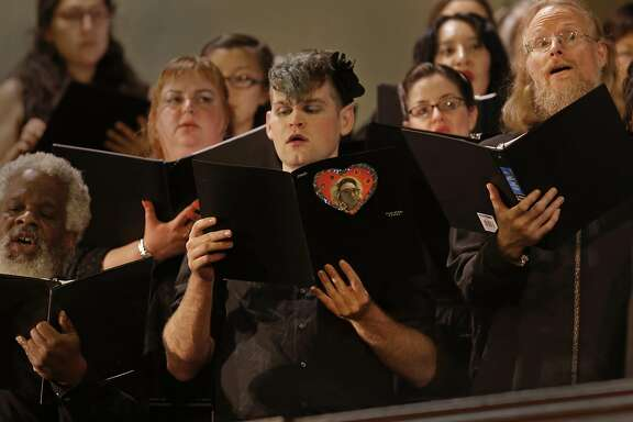 "Tenor, Yacob McCann holds his song book containing a photo of his friend and fellow chorus member Denalda Siegrist during the performance as Laney College's Oakland City Chorus holds "" A Time for Reflection"" at the First Presbyterian Church in Oakland, California, on Friday  December 9, 2016. The benefit was held for chorus member Denalda Siegrist and other victims who perished in the Ghost Ship warehouse fire."
