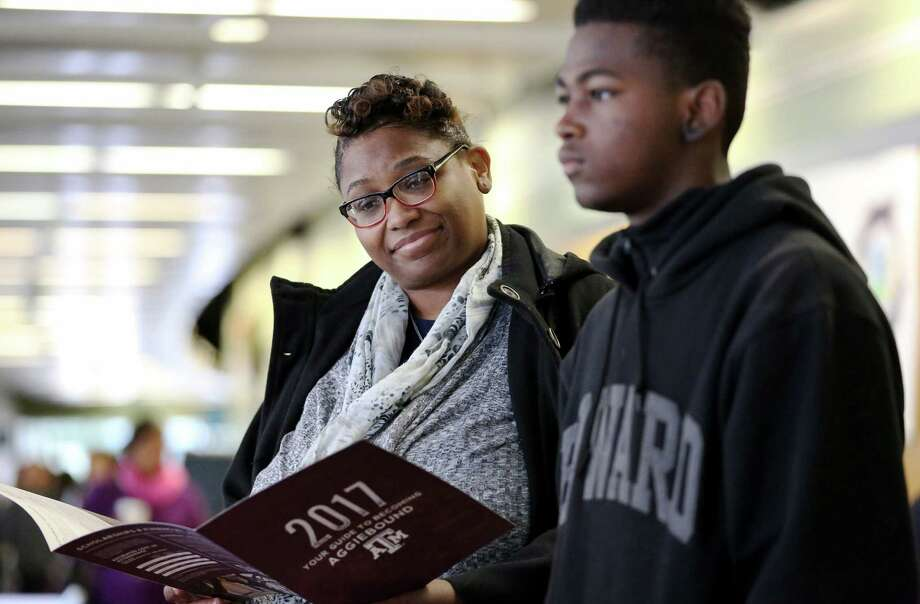 Shawnda Smith looks through Texas A&M's program package while her son, Tariq Powell, 16, talks to Texas A&M representative at Houston Independent School District's second DREAM Summit Saturday, Dec. 10, 2016, in Houston. Tariq, a junior at Chavez High School, is interested in the school's engineering program. Photo: Yi-Chin Lee, Houston Chronicle / © 2016  Houston Chronicle