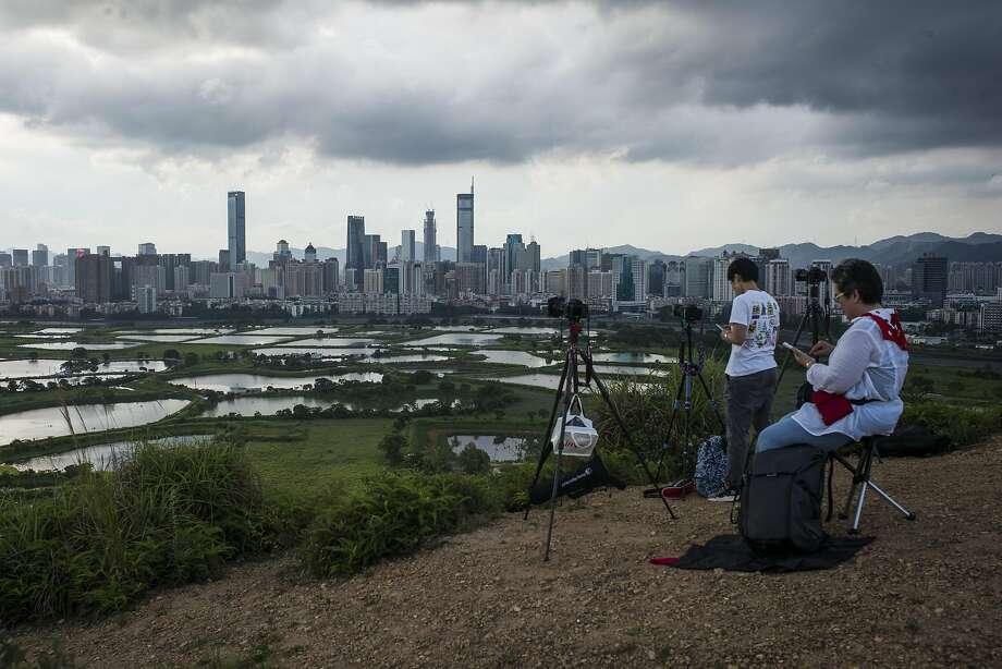 Photographers shoot the Shenzhen - Hong Kong border at dusk in the Ma Tso Lung district of Hong Kong, China, on Thursday, June 8, 2017. Shenzhen is pivoting from its legacy as ground zero for China's manufacturing boom into a center for research, development and production of advanced technology. Photographer: Justin Chin/Bloomberg Photo: Justin Chin, Bloomberg