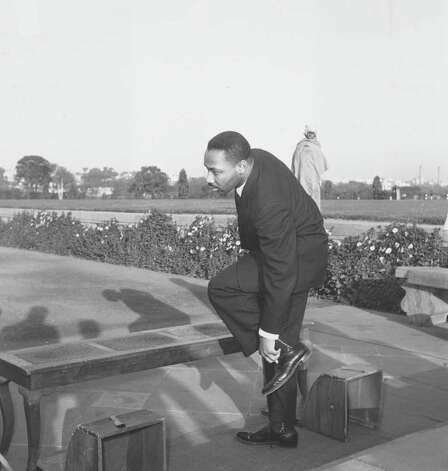 American civil rights leader Rev. Martin Luther King Jr. removes his shoes before entering Mahatma Gandhi's shrine in New Delhi, India, Feb. 11, 1959.  (AP Photo) / Beaumont
