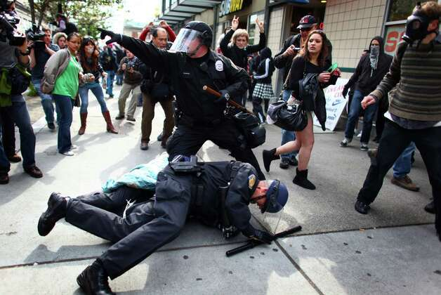Officers arrest a man that threw a glass jar and hit an officer in his faceshield during a May Day rally on Tuesday, May 1, 2012 in downtown Seattle. The rally turned violent when black-clad protesters smashed windows and threw objects at police. One officer was hit in the head with a glass bottle. Photo: JOSHUA TRUJILLO / SEATTLEPI.COM