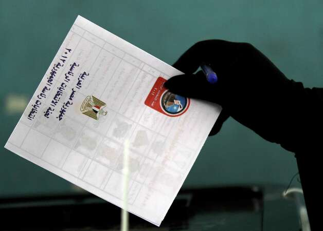 """An Egyptian voter casts her ballot in an historic presidential election Wednesday at a polling station in Cairo, Egypt. The ballot, in Arabic, reads, """"the Republic of Egypt polling station for the presidency."""" Nearly a year and a half after the ouster of autocratic leader Hosni Mubarak, millions of Egyptians lined up for hours outside polling stations Wednesday to freely choose a president for the first time in an election that pits old regime figures promising stability against ascending Islamists seeking to consolidate power. (AP Photo/Hasan Jamali) Photo: Hasan Jamali, Associated Press / AP2012"""