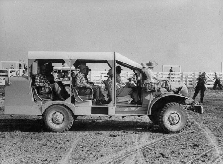 A group of quail hunters riding in a converted truck during a visit on a ranch in 1956.