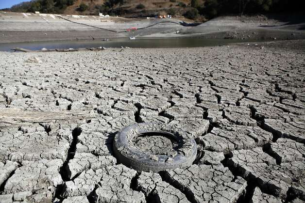A discarded tire is seen stuck in the exposed lake bed of the Almaden Reservoir which is experiencing extremely low water levels due to the ongoing drought, in San Jose. Photo: Michael Short, The Chronicle