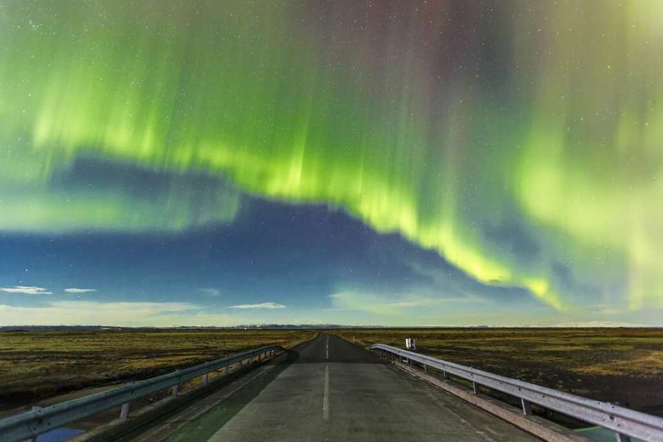 Aurora Borealis over a road near Vik in Southern Iceland. When charged particles get excited, they show it by emitting neon colors.Loop Images/UIG via Getty Images. Photo: Loop Images, UIG Via Getty Images