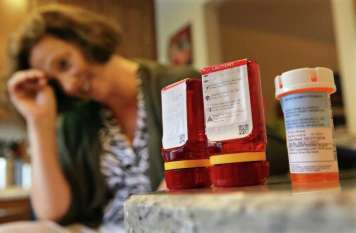 In this Sunday, Sept. 18, 2016, photo, Shelley Ewalt sits in her home, in Princeton, N.J., near an amber-colored CVS pharmacy prescription bottle, right, and two uniquely designed red ones from Target. After CVS took over operation of Target's drugstores earlier this year, distraught customers have been asking the drugstore chain to bring back the retailer's red prescription bottles, which came with color-coded rings, labeling on the top and prescription information that was easier to read. Ewalt tweeted to the drugstore chain, asking if there was any chance they might return to the design of the Target bottles, which she found easier to open. (AP Photo/Mel Evans) ORG XMIT: NJME251 Photo: Mel Evans / Copyright 2016 The Associated Press. All rights reserved.