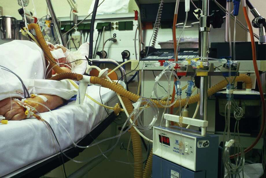 "The ""End-of-Life Conveyor Belt"": Dying patients are kept alive by machines, alone in a cold and sterile environment, their arms strapped down to the bed so that their catheters aren't dislodged. Photo: Getty Images, Jan Halaska / This content is subject to copyright."