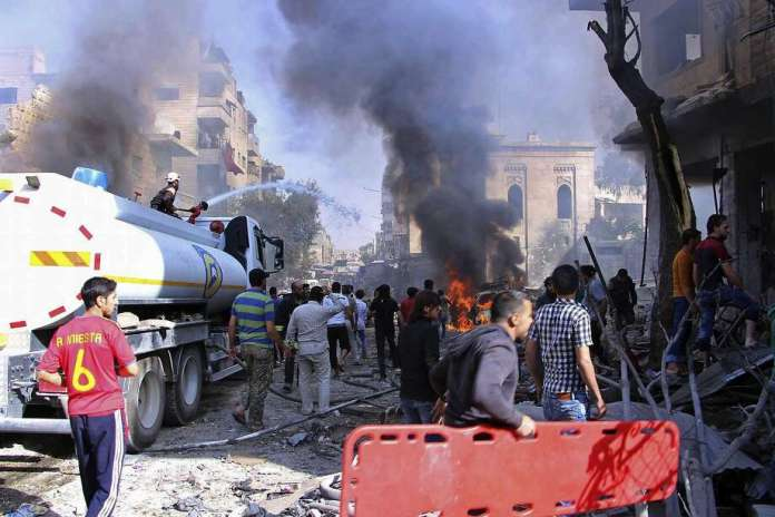 Syria Civil Defense workers, known as White Helmets, battle a fire from an air strike on a market in southern Idlib province. Photo: Associated Press