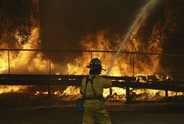 A firefighter sprays a hose into a Keysight Technologies building in Santa Rosa. More than 100 boxes containing letters and other documents from Hewlett-Packard founders William Hewlett and David Packard were incinerated when the Tubbs fire tore through one building on Keysight's campus. Photo: Jeff Chiu, Associated Press