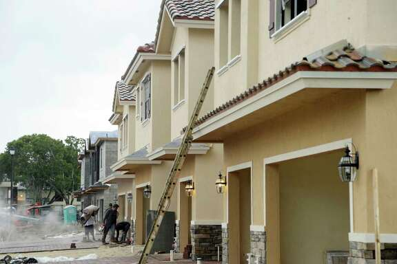Lennar Corp. townhomes are under construction in 2016 in Tamarac, Fla. Lennar is buying CalAtlantic Group in a deal that would create the nation's largest homebuilder. The industry still grapples with expenses that make building homes - especially starter homes - too costly, housing experts say.