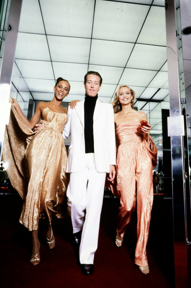 Halston with models Alva Chinn and Chris Royer in evening wear from his 1978 Resort collection at Halston's Olympic Towers headquarters in New York.