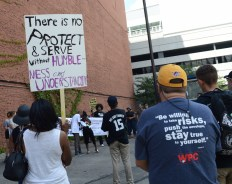 """a gathering of people between buildings. multiracial crowd is listening to a person holding a megaphone. people have signs and expressive t-shirts. most prominently visible is a sign held high stating """"there is no protective and serve without humbleness and understanding""""."""