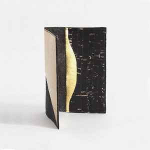 Side view of the Delia Passport cover in Piñatex Cork Black and Gold
