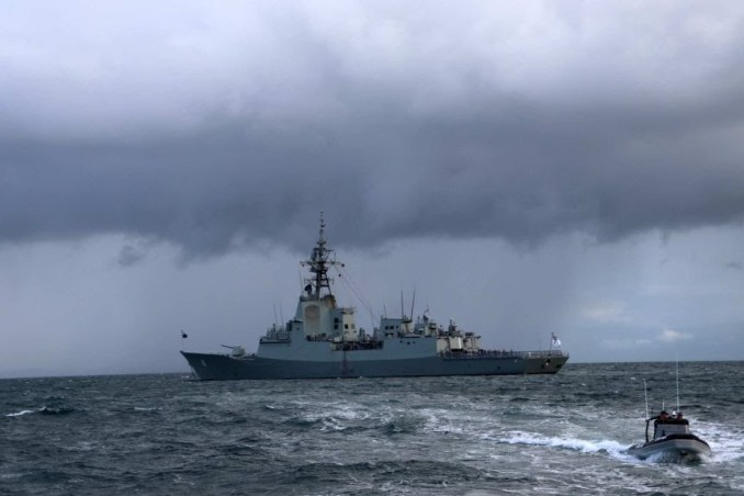 HMAS Brisbane with dark clouds behind it.