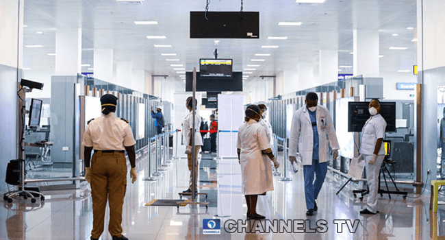 A security official and medical personnel move around at the Nnamdi Azikwe International Airport in Abuja. Photo: Sodiq Adelakun / Channels TV