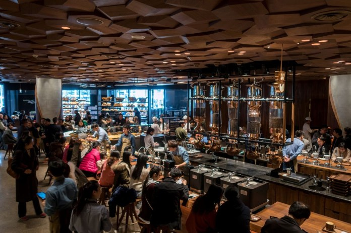 Visitors wait for their coffee at the Starbucks Reserve Roastery outlet in Shanghai on Dec. 6, 2017, the store's opening day.