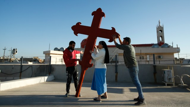 Image: Hadi Mizban / AP Photo. Iraqi Christians place a cross on a church in Qaraqosh on February 22 in advance of Pope Francis' visit to Iraq next month.