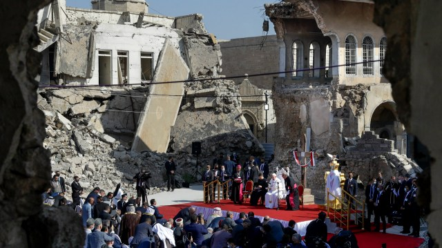 Image: Andrew Medichini / AP - Pope Francis, surrounded by shells of destroyed churches, leads a prayer for the victims of war at Hosh al-Bieaa Church Square in Mosul, Iraq, once the de-facto capital of ISIS, on March 7, 2021.