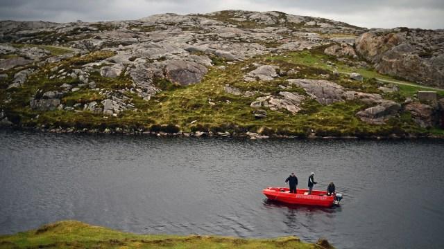 Men fly fish in a boat on a loch in Harris.