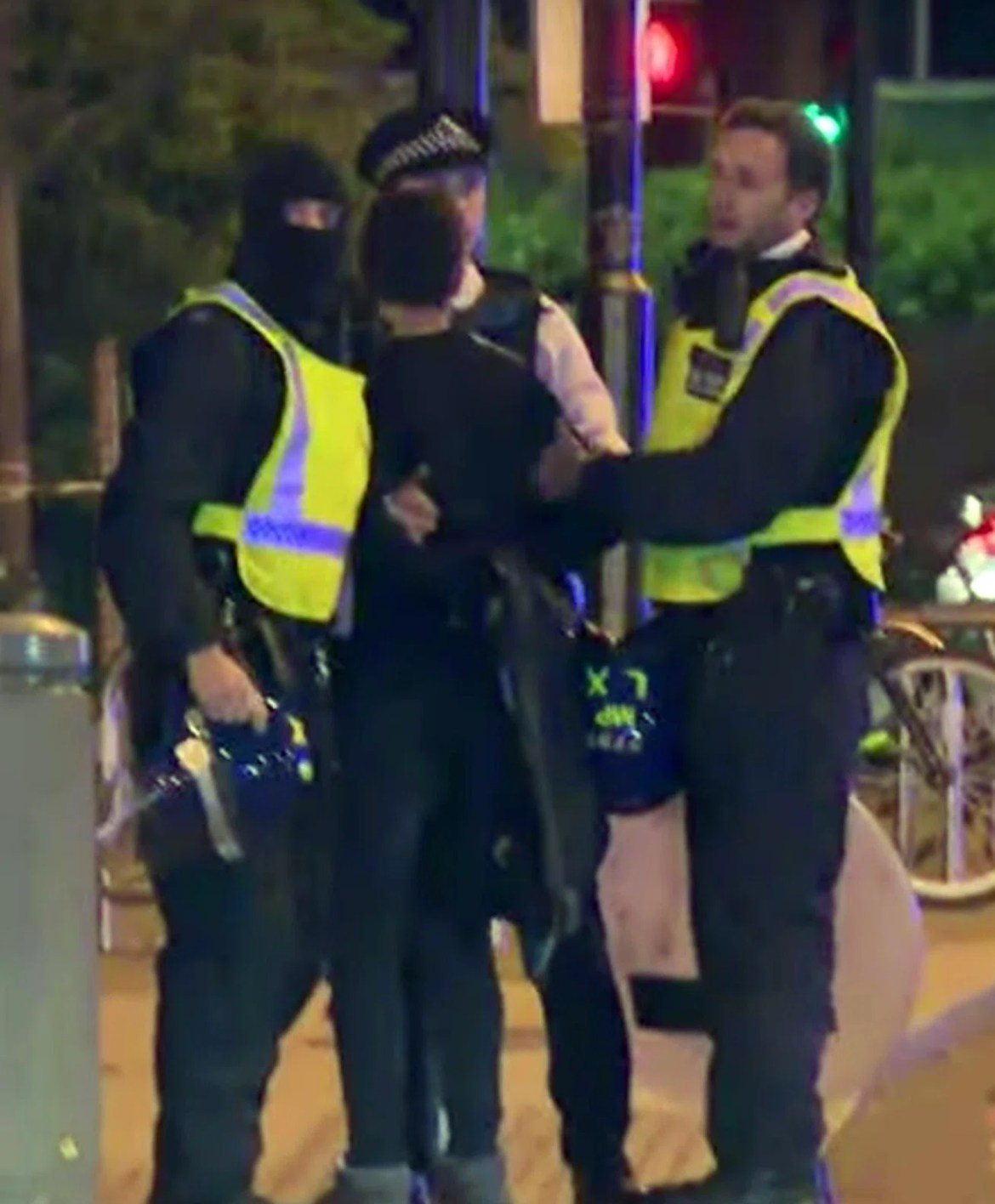Three cops, one of whom is masked, are pictured arresting the suspect